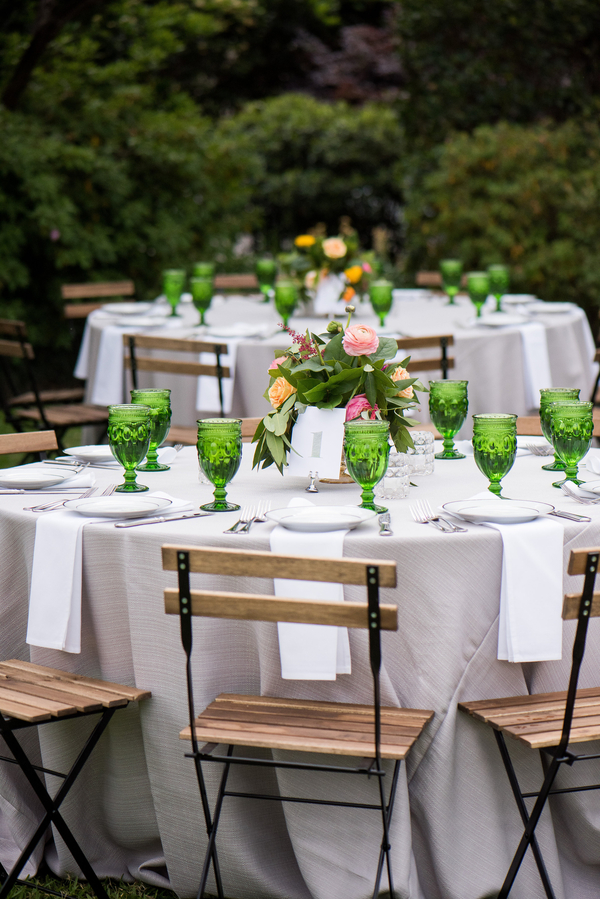 Wedding reception table with green goblet glasses