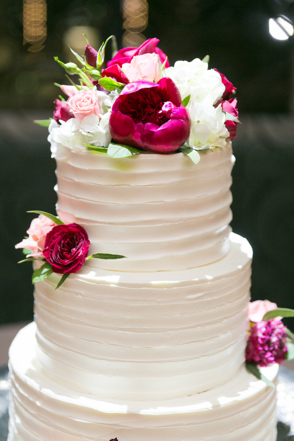 White buttercream cake with deep purple flowers